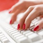 Get Well Guru Woman's fingers typing on keyboard