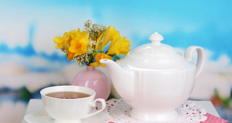 White tea set with yellow flowers and blue sky background