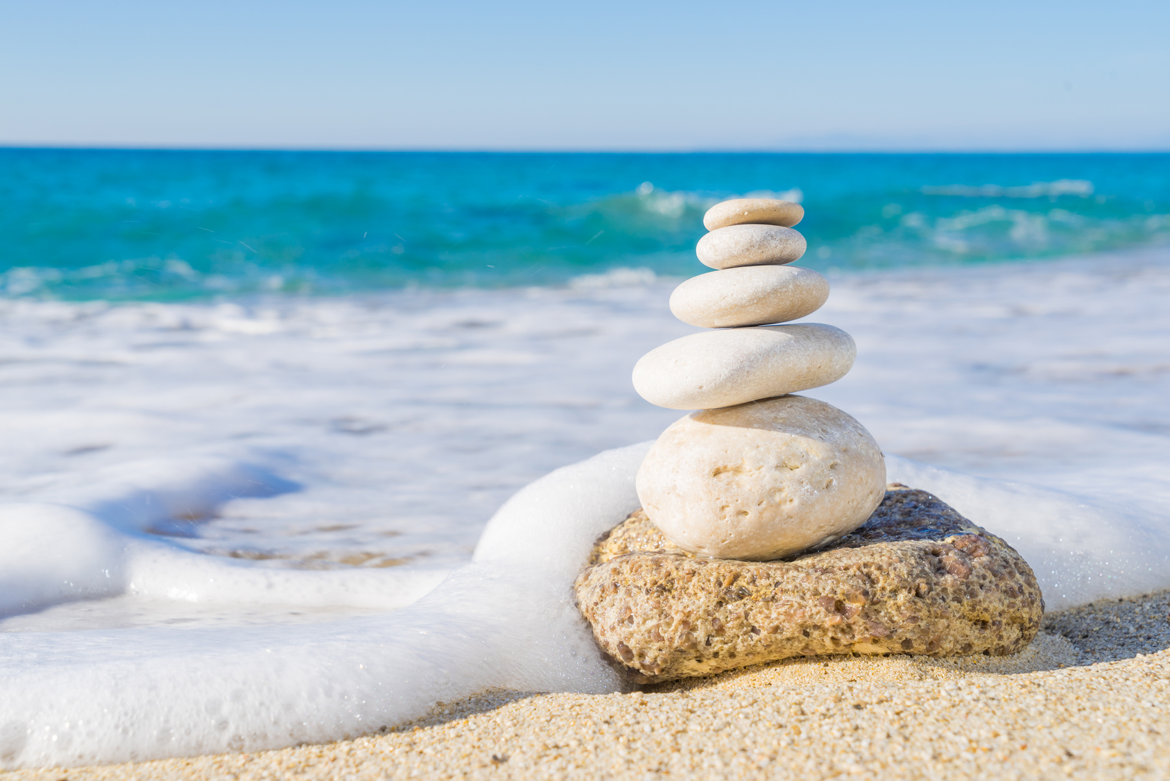 ocean with foam and stacked rocks on a beach, mindfulness meditation